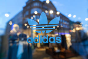 The Adidas logo sits on a window at an Adidas AG originals store in Berlin, Germany, on Wednesday, March 4, 2015