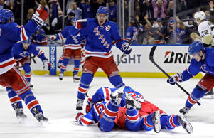 New York Rangers' Dan Girardi, Ryan McDonagh, middle, and Jesper Fast celebrate with New York Rangers' Carl Hagelin, bottom middle, after game five against the Pittsburgh Penguins April 24 in New York. The Rangers won 2-1 after Hagelin scored in overtime.