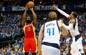Houston Rockets guard James Harden (13) shoots a three point basket against Dallas Mavericks guard Monta Ellis (11) and forward Dirk Nowitzki (41) in game three of the first round of the NBA Playoffs at American Airlines Center. The Rockets beat the Mavs 130-128.