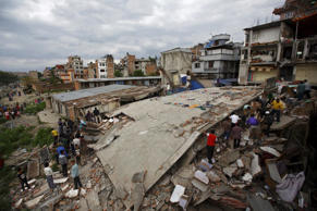 People gather near a collapsed house after a major earthquake in Kathmandu, Nepal, on April 25, 2015.
