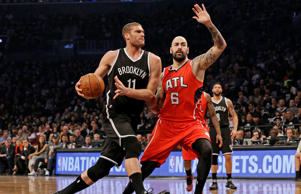 Brooklyn Nets center Brook Lopez, left, drives to the basket against Atlanta Hawks forward Pero Antic during the first half in Game 3 of a first-round NBA basketball playoff series, Saturday, April 25, 2015, at New York.