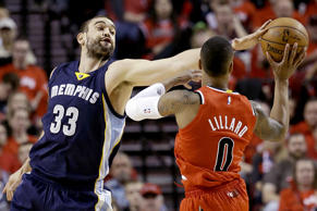 Memphis Grizzlies center Marc Gasol, left, gets a piece of the ball while defending Portland Trail Blazers guard Damian Lillard during the first half of Game 3 of a first-round NBA basketball playoff series in Portland, Ore., Saturday, April 25, 2015.