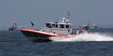 A Coast Guard patrol boat zips across Mobile Bay as shrimpers fish the bay, June 12, 2013.