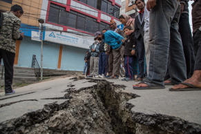 Residents look at a crack in the pavement on April 26, 2015 in Kathmandu.