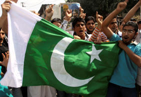 File Photo: Kashmiri people hold a flag of Pakistan and shout freedom slogans during celebrations marking Pakistani Independence Day in Srinagar, India, Friday, August 14, 2009