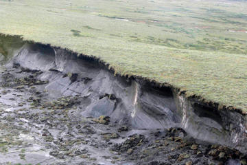 "In this Aug. 10, 2009, photo, a hill of permafrost ""slumping"" from global warming near the remote, boggy fringe of North America, 2,200 kilometers (1,400 miles) from the North Pole, where researchers are learning more about methane seeps in the 25,000 lakes of this vast Mackenzie River Delta, in the Northwest Territories, Canada."