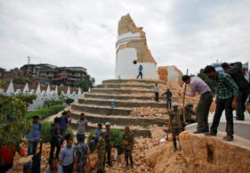 Volunteers work to remove debris at the historic Dharahara tower, a city landmark, after an earthquake in Kathmandu, Nepal, Saturday, April 25, 2015. A strong magnitude-7.9 earthquake shook Nepal's capital and the densely populated Kathmandu Valley before noon Saturday, causing extensive damage with toppled walls and collapsed buildings, officials said.