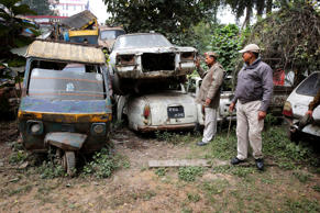 File: Policemen take an account of accident cars parked at their police station in Allahabad, India, Friday, Jan. 31, 2014.