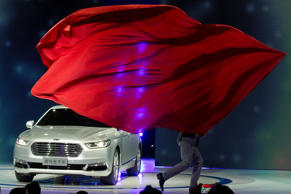 A performer unveils the Ford Taurus during the Shanghai Auto Show in Shanghai.