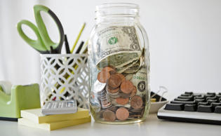 Jar full of money on desk. Jamie Grill/Tetra images RF/Getty Images