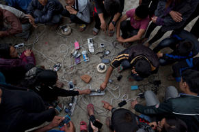 Nepalese villagers charge their cell phones in an open area in Kathmandu, Nepal, Monday, April 27, 2015. Shelter, fuel, food, medicine, power, news, workers — Nepal's earthquake-hit capital was short on everything Monday as its people searched for lost loved ones, sorted through rubble for their belongings and struggled to provide for their families' needs.