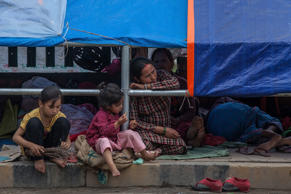 File: A family take shelter on a sidewalk in the city centre on April 27, 2015 in Kathmandu, Nepal. A major 7.8 earthquake hit Kathmandu mid-day on Saturday, and was followed by multiple aftershocks that triggered avalanches on Mt. Everest that buried mountain climbers in their base camps. Many houses, buildings and temples in the capital were destroyed during the earthquake, leaving over 3000 dead and many more trapped under the debris as emergency rescue workers attempt to clear debris and find survivors.