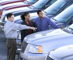 A salesman pointing out features of new cars to a interested couple