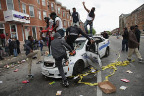 File: Demonstrators climb on a destroyed Baltimore Police car in the street near the corner of Pennsylvania and North avenues during violent protests following the funeral of Freddie Gray April 27, 2015 in Baltimore, Maryland.