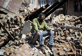 A man sits on the rubble of his damaged house following Saturday's earthquake in Bhaktapur, Nepal April 27, 2015. REUTERS/Adnan Abidi