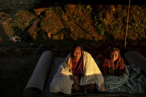 Local villagers sit inside their makeshift shelter near a devastated area following Saturday's earthquake, at Paslang village, Nepal.