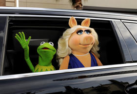Kermit the Frog and Miss Piggy wave to the crowd as they arrive in cars on the red carpet Tuesday, March 11, 2014, in Los Angeles.