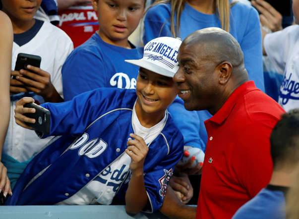 "Los Angeles Dodgers owner Earvin ""Magic"" Johnson poses for a selfie cell phone photo with a young fan before the baseball game between the Los Angeles Dodgers and San Francisco Giants at Dodger Stadium on April 28 in Los Angeles."