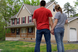 Couple outside large home