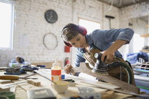 Carpenter using sander on wood in workshop. Hero Images/Getty Images