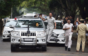 File: A security officer hangs on to the car carrying former chief minister of Tamil Nadu state Jayaram Jayalalitha after she was released from prison in Bangalore, India, Saturday, Oct. 18, 2014.