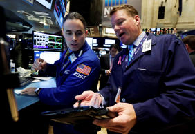 Trader Jason Hardzewicz, left, and trader John Bowers work on the floor of the New York Stock Exchange.