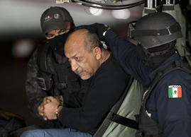 "Federal police escort who they identify as Servando ""La Tuta"" Gomez,"" leader of the Knights Templar cartel, as he sits inside helicopter at a Federal hanger in Mexico City, Friday, Feb. 27, 2015. Gomez, a former school teacher who became one of Mexico's most-wanted drug lords as head of the Knights Templar cartel, was captured by federal police, according to Mexican officials."