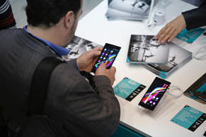 A visitor inspects a smartphone on display in the Wiko pavilion at the Mobile World Congress in Barcelona, Spain, on March 3, 2015.