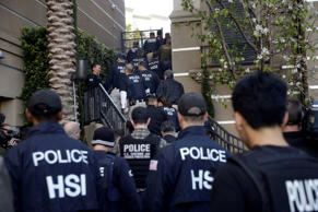 Federal agents enter an upscale apartment complex, Tuesday, March 3, 2015, in Irvine, Calif. Shortly after sunrise, federal agents swarmed the complex in the Orange County where authorities say a birth tourism business charged pregnant women $50,000 for lodging, food and transportation. The key draw for travelers is that the United States offers birthright citizenship.
