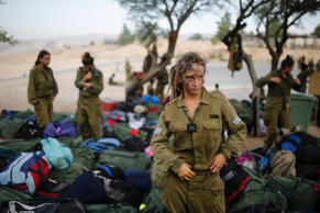 An Israeli soldier of the Caracal battalion stands next to backpacks after finishing a 20-kilometre march in Israel's Negev desert, near Kibbutz Sde Boker on May 29, 2014.