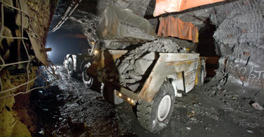 A front end loader dumps a bucketfull of copper/nickel ore into a 40-ton truck.