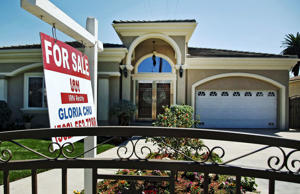 "A ""For Sale"" sign is posted on a home in Monterey Park, Calif."