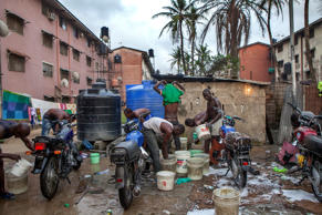 A view of one of the many neighborhood public spaces that have been converted into a motorcycle washing station, against the master plan of the Festac town.