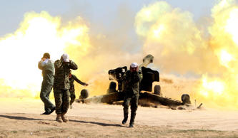 Volunteer Shiite fighters, known as the Popular Mobilisation units, who support the Iraqi government forces in the combat against the Islamic State (IS) group, fire a Howitzer artillery canon in the village of Awaynat near the city of Tikrit on February 28, 2015. Government forces have attempted and failed several times to wrest back Tikrit -- the hometown of former president Saddam Hussein -- since losing it to IS in June 2014.