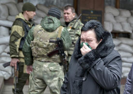 A woman reacts as she walks past pro-Russian rebels guarding the Zasyadko mine in Donetsk, Ukraine Wednesday March 4, 2015. An explosion at the Zasyadko coal mine in war-torn eastern Ukraine killed 32 workers on Wednesday, the speaker of Ukraine's parliament said. Rebels who control the area, however, confirmed only one death.