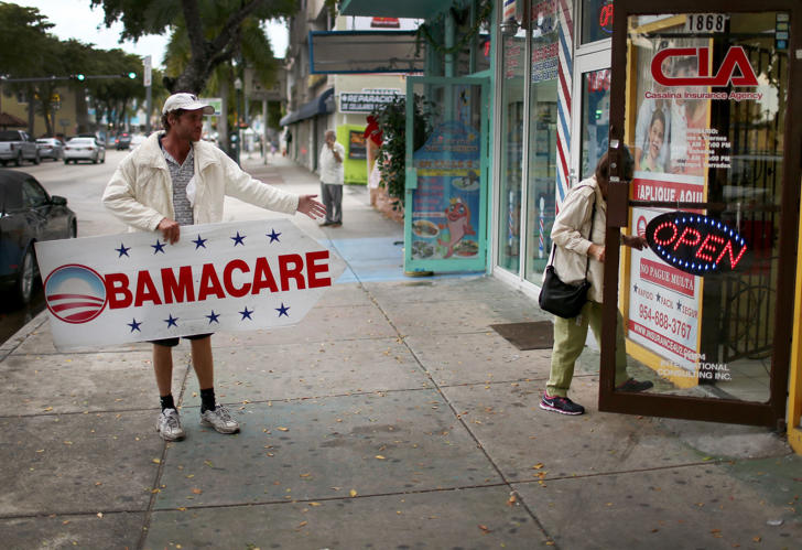 A man holds a sign directing people to an insurance company where they can sign up for the Affordable Care Act, also known as Obamacare, before the February 15th deadline on February 5, 2015 in Miami, Florida.