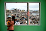 A victim from super typhoon Haiyan holds her one year old daughter overlooking her flattened home and devastated waterfront community from a partial standing building in Tacloban on November 24, 2013.