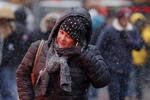 A woman covers up from the snowfall at Times Square in New York March 3, 2015. A weather pattern next week should bring warmer temperatures to the Northeast and Central United States.