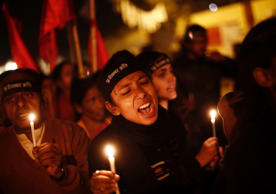 Protestors shout slogans as they hold candles during a candle light vigil to mark the first anniversary of the Delhi gang rape, in New Delhi, December 16, 2013.
