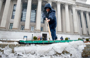 National Archives maintenance worker Douglas Ramirez pushes slush off the sidewalk along Pennsylvania Avenue in Washington, Thursday, March 5, 2015, as snow begins to fall.