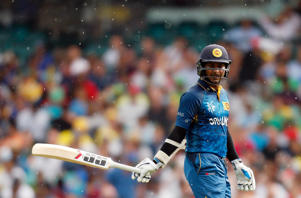 Rain starts to fall as Sri Lanka's Kumar Sangakkara walks off the field after being caught by South Africa's David Miller for 45 runs during their Cricket World Cup quarter-final match at the Sydney Cricket Ground (SCG) March 18, 2015.
