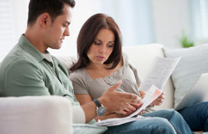 Hispanic couple reviewing monthly bills finances