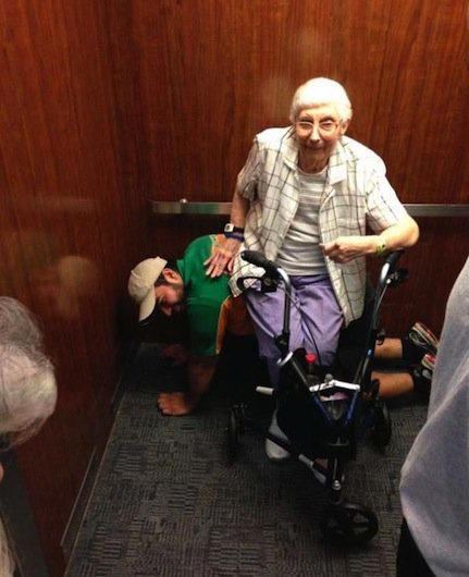 A college student gets on his hands and knees to serve as a human bench for an elderly woman.