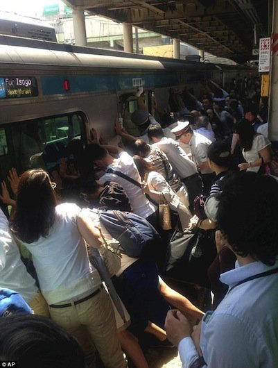A crowd pushes against a train to rescue a stranger caught in the gap between the train and the platform.