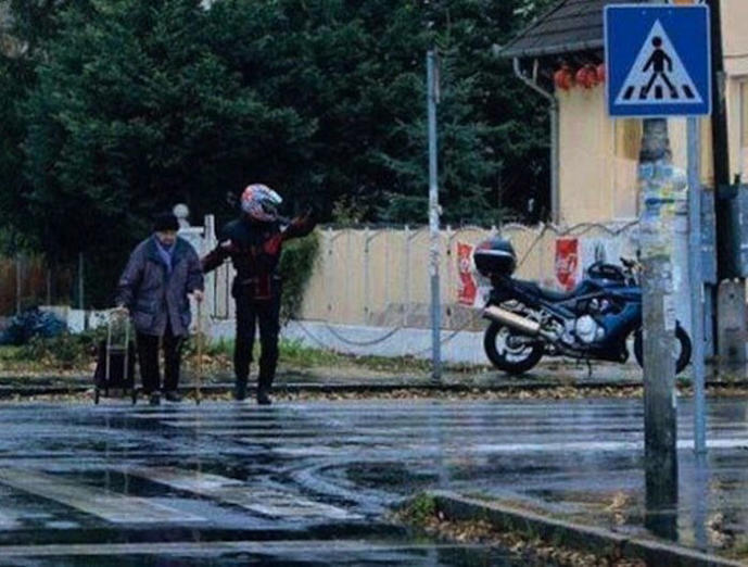 A motorcyclist pulls over to help an elderly lady cross the street on a rainy day.