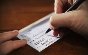 Man writing a donation check to a charitable organization. donald_gruener/Getty Images