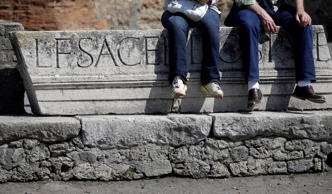 Tourists sit on a ruins at he Pompeii ancient site near the Villa of Mysteries on the occasion of its presentation to journalists in Pompeii, Italy, Friday, March 20, 2015. Italy unveiled the restored crown jewel of the ancient city of Pompeii, the Villa of Mysteries, on Friday, showing off a rare success story as it races to shore up the site that has been marred by such mismanagement that it risked losing EU funding and being delisted as a UNESCO world heritage site. (AP Photo/Gregorio Borgia)