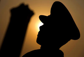A Chinese paramilitary policeman is silhouetted as he stands near the Monument to the People's Heroes on Tiananmen Square before the annual National People's Congress in Beijing, Thursday, March 5, 2015. China announced a lower economic growth target for this year and promised to open more industries to foreign investors as it tries to make its slowing, state-dominated economy more productive.
