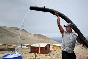 LIMA, PERU - JANUARY 21:  A Peruvian water distribution worker with a pipe fills a tank with drinking water on the dusty hillside of Pachacútec, a desert suburb, on January 21, 2015 in Lima Peru. Although Latin America is blessed with an abundance of fresh water, having 20% of global water resources in the Amazon Basin and the highest annual rainfall of any region in the world, an estimated 50-70 million Latin Americans (one-tenth of the continent's population) lack access to safe water and 100 million people have no access to any safe sanitation. Complicated geographical conditions, unregulated industrialization and massive urban poverty, combined with deep social inequality, have caused a severe water supply shortage in many Latin American regions. (Photo by Jan Sochor/LatinContent/Getty Images)