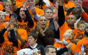 President Barack Obama, center, and his brother-in-law Craig Robinson, right, react as Princeton scores against Wisconsin-Green Bay during a women's college basketball game in the first round of the NCAA tournament in College Park, Md., Saturday, March 21, 2015. Obama's niece Leslie Robinson, plays for Princeton.